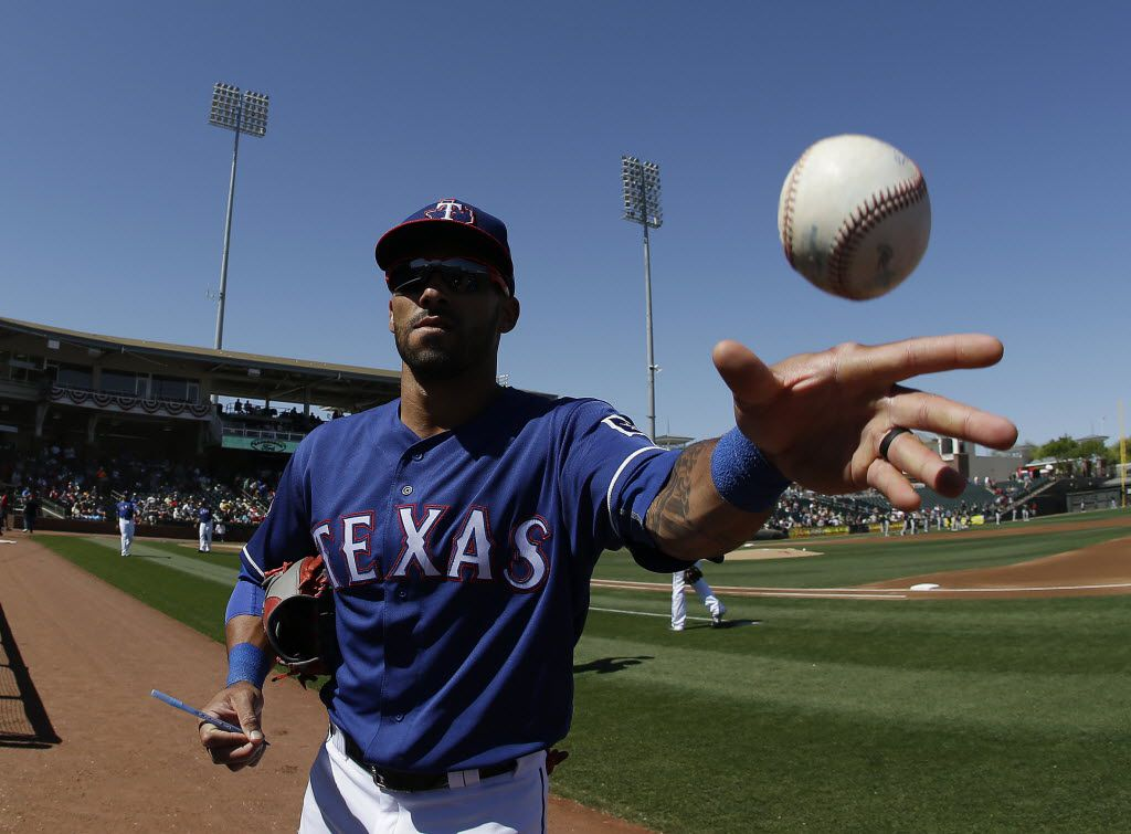 Texas Rangers' Ian Desmond tosses a baseball to a fan before a spring training baseball game against the Oakland Athletics on Saturday, March 12, 2016, in Surprise, Ariz. (AP Photo/Darron Cummings)