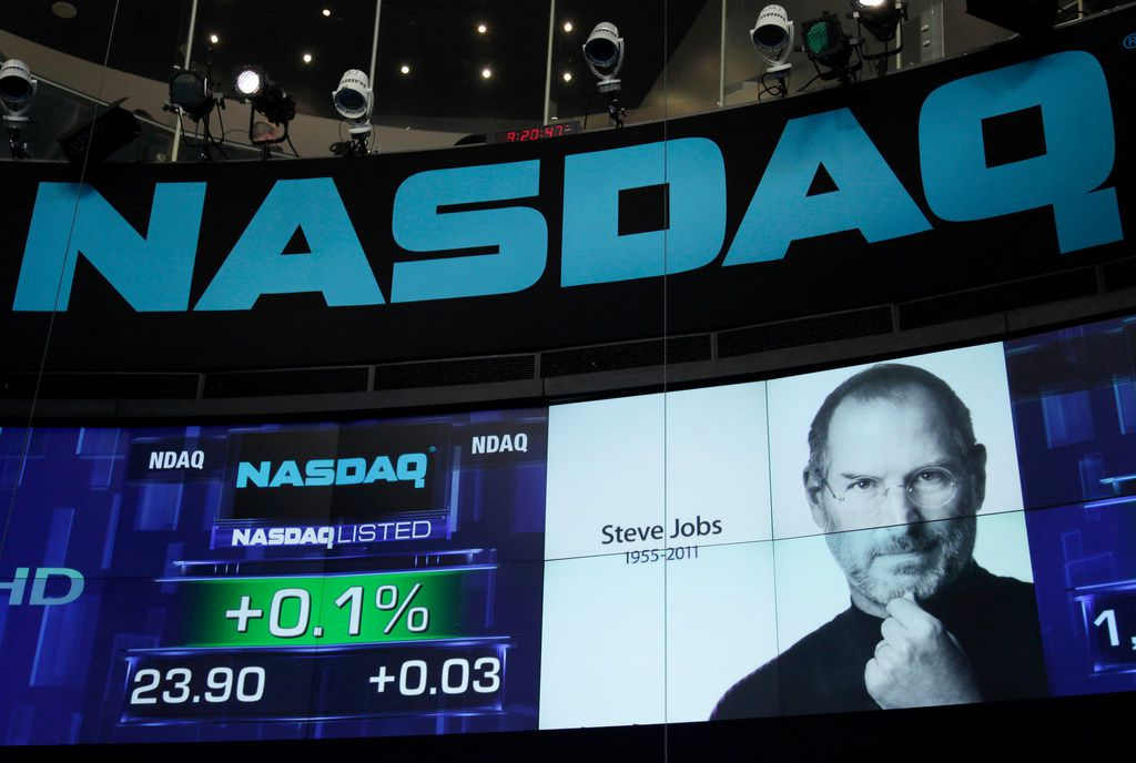 FILE - In this Oct. 6, 2011 file photo, a photo of Apple co-founder Steve Jobs is displayed as a tribute at Nasdaq in New York. Jobs died Wednesday at age 56 after a long battle with cancer.  Apple has become the world's first company to be valued at $1 trillion, the financial fruit of tasteful technology that has redefined society since two mavericks named Steve started the company 42 years ago. (AP Photo/Mark Lennihan)