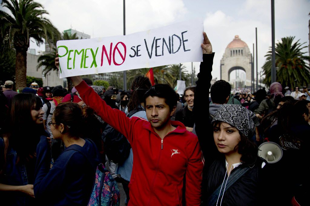 """A couple holds up a banner about Mexico's state-owned oil company that says, """"PEMEX is not for sale"""" in Mexico City. (2013 File Photo/The Associated Press)"""