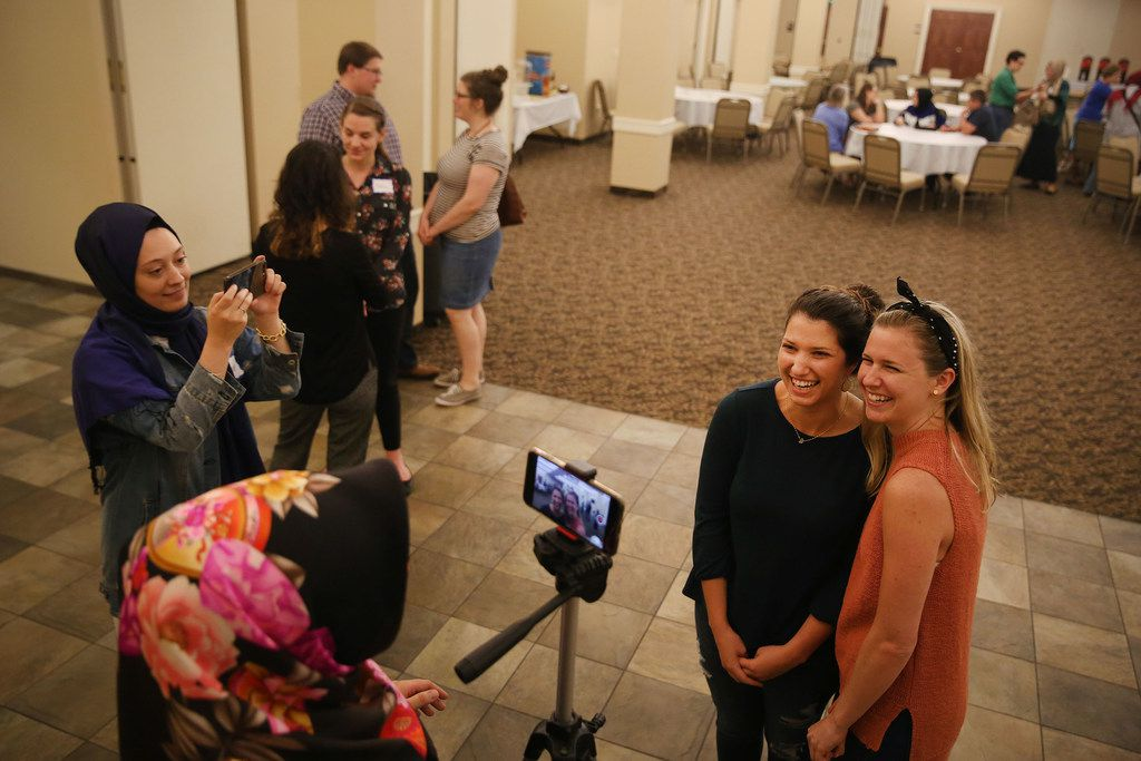 Seniha Yildirim (bottom) films Amanda Mintz (second to right) and Lydia Pettit (right) as she asks them about their experience learning about Ramadan during an interfaith Ramadan dinner with members of the Dialogue Institute and Wilshire Baptist Church at the church in Dallas Thursday June 7, 2018. Guests broke the Ramadan fast after Emrah Aktepe, who is director of the Dialogue Institute Dallas, explained Ramadan.