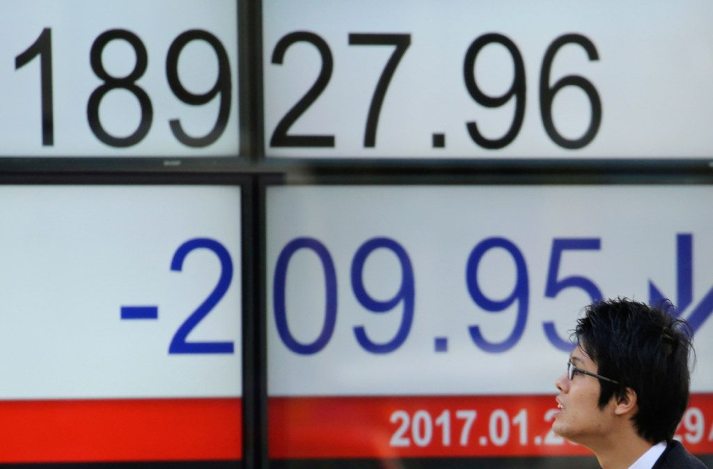 """A man looks at an electronic stock board of a securities firm in Tokyo, Monday, Jan. 23, 2017. Japanese stocks tumbled Monday after Donald Trump took office as U.S. president and promised """"American first"""" policies, prompting concern about possible protectionism. (AP Photo/Koji Sasahara)"""