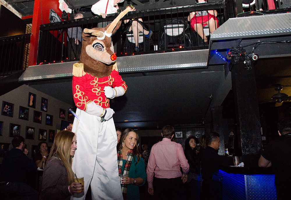 A stilted Rudolph poses with attendees at the 5th annual Nearly Naked Nutcracker.