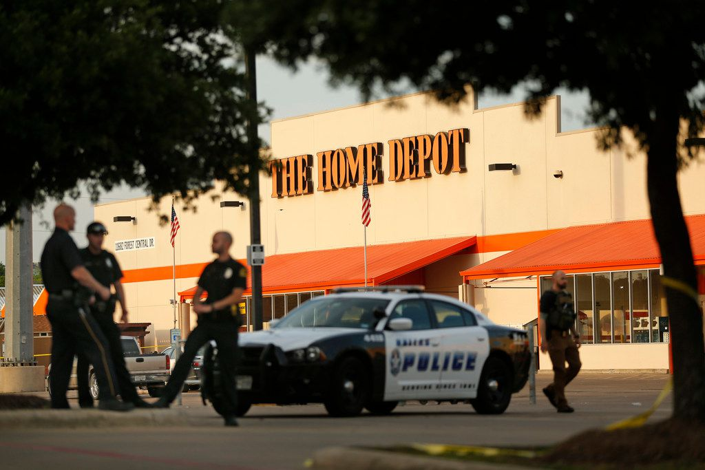 Dallas police officers stood guard Tuesday at the Home Depot where their colleagues were shot.