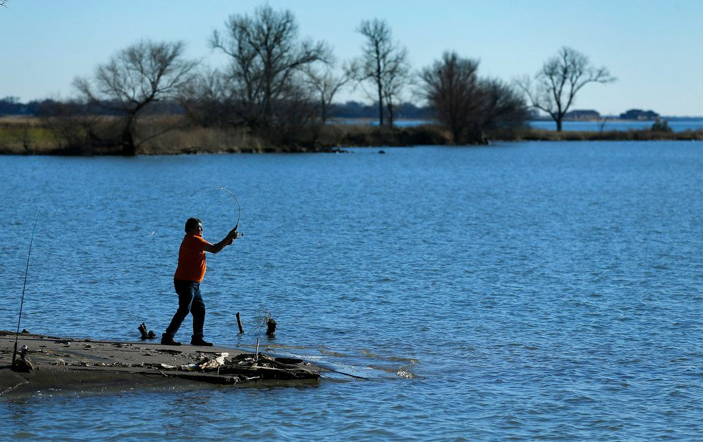 Fisherman Jose J Torres of Dallas cast his line near the Bayside development under construction on the Lake Ray Hubbard peninsula south of Interstate 30 in Rowlett, Texas, Friday, January 4, 2019. Mayor Tammy Dana-Bashian spoke of the city's lawsuit against Bayside Land Partners LLC and Bayside District Partners LLC over what they say is a default in development agreements after months of unsuccessful discussions about the 262-acre Bayside development, which includes Crystal Lagoon. (Tom Fox/The Dallas Morning News)