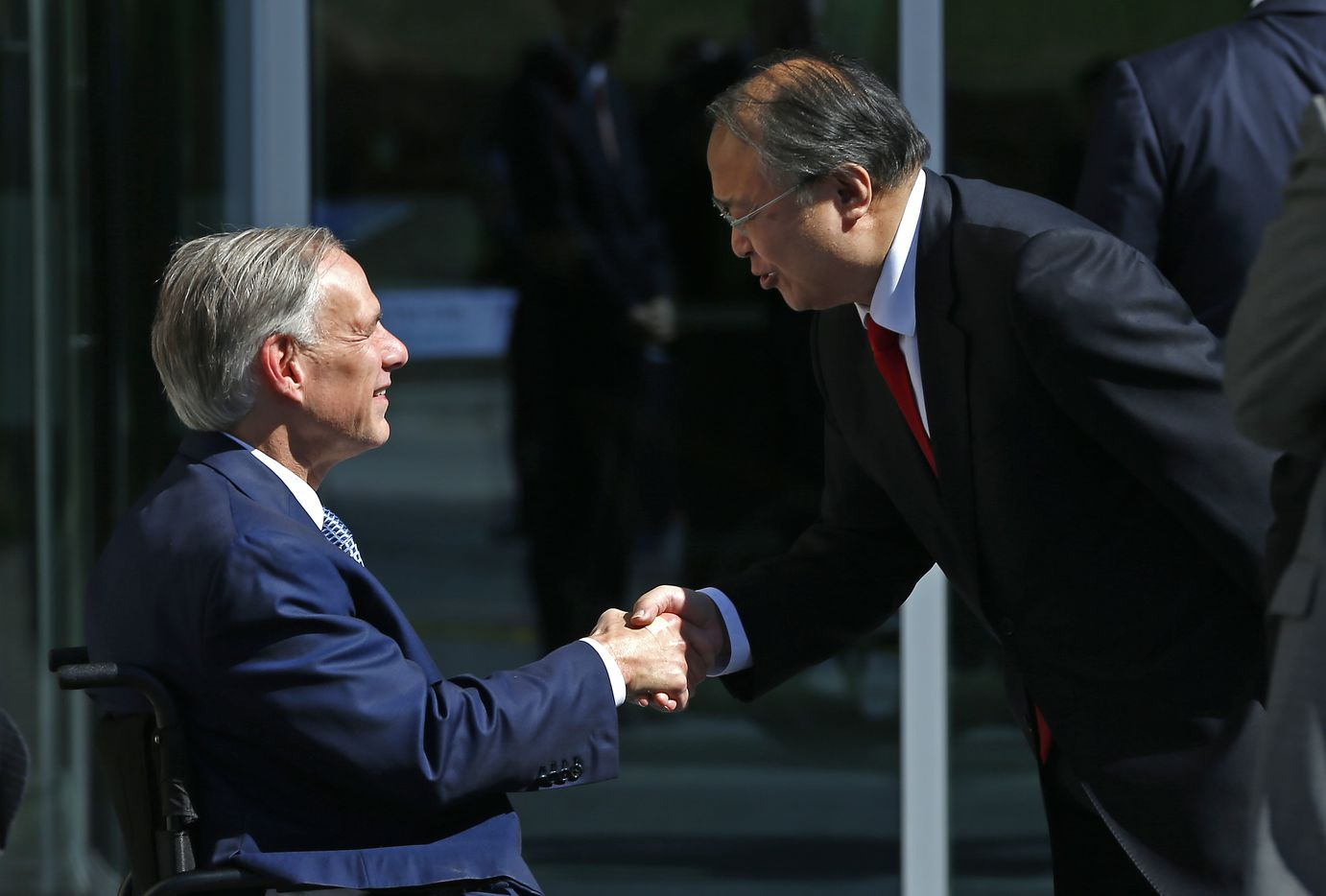 Texas Gov. Greg Abbott shakes hands with Consulate-General of Japan Teruo Amano during a ribbing cutting ceremony at the new Kubota Tractor Corp. headquarters in Grapevine.