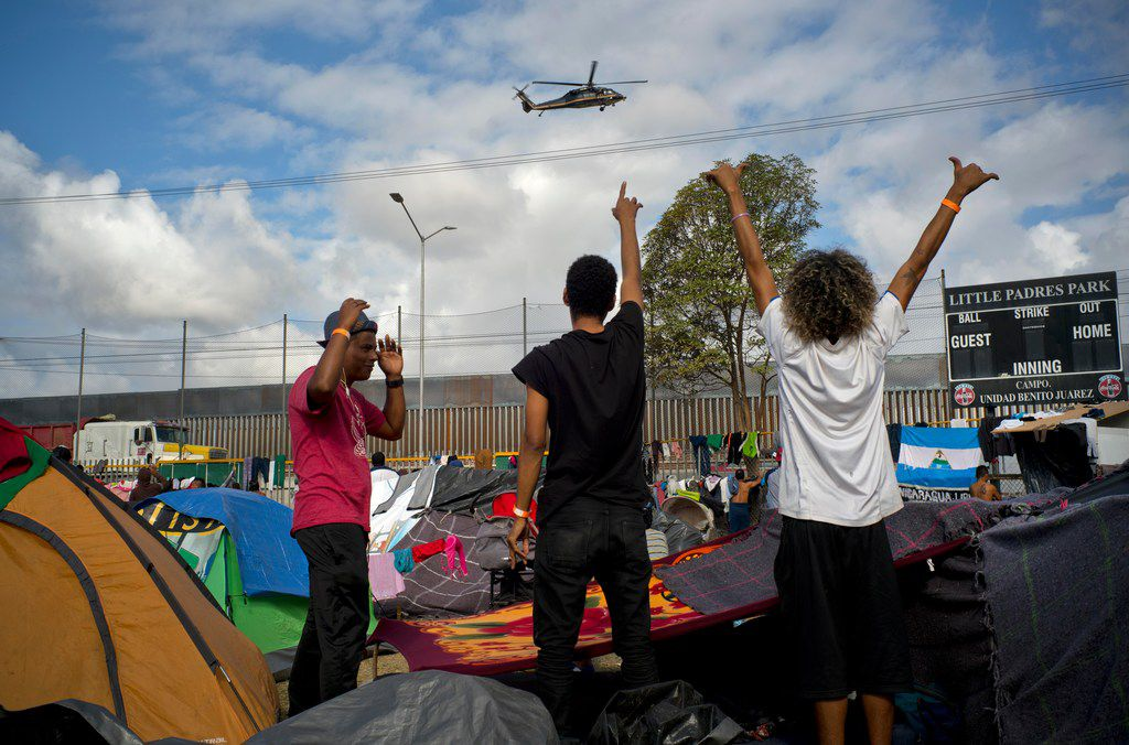 Migrants wave at U.S. border control helicopters flying near the Benito Juarez Sports Center serving as a temporary shelter for Central American migrants, in Tijuana, Mexico, on Nov. 24, 2018.