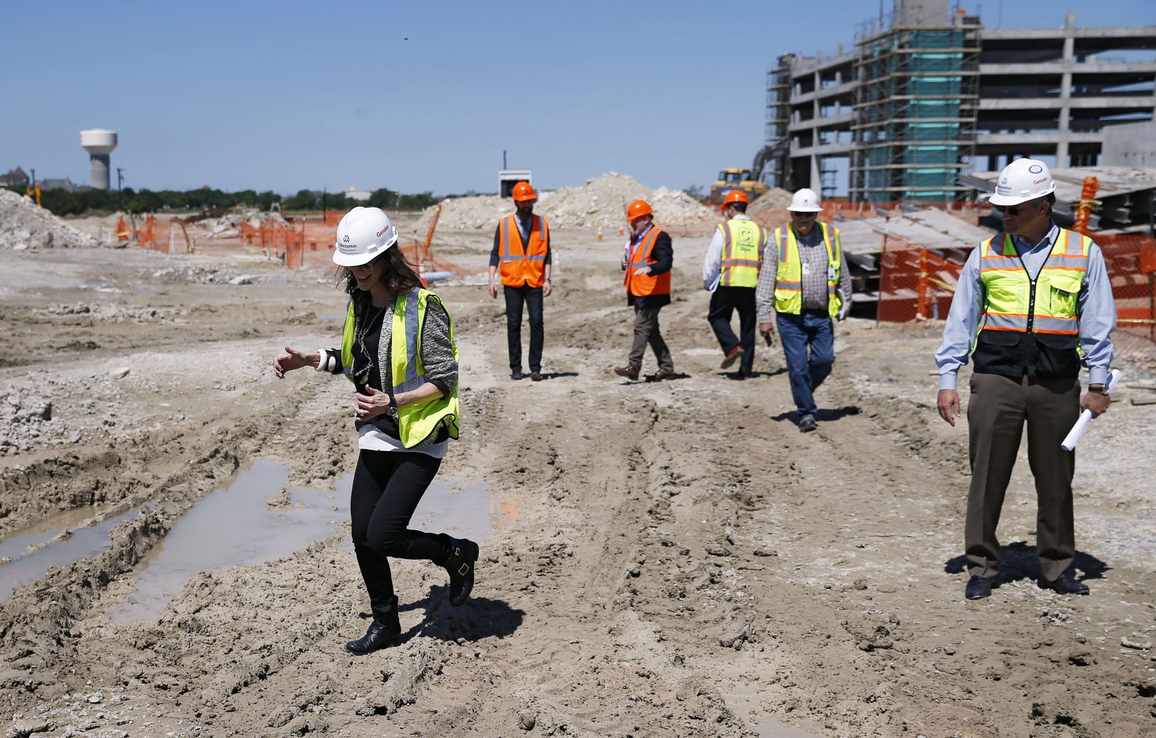Charlotte Jones Anderson (center) Executive Vice President and Chief Brand Officer for the Dallas Cowboys makes her way around a muddy area as Senior Director Jennifer Surgalski, Corporate Partnership Services Dallas Cowboys and Project Manager, Mark Hickman of Legends watch during a tour of signs for use at the Dallas Cowboys new headquarters at The Star in Frisco, on Tuesday, May 3, 2016. The Star a joint project with the City of Frisco is scheduled to open in August. (Vernon Bryant/The Dallas Morning News)