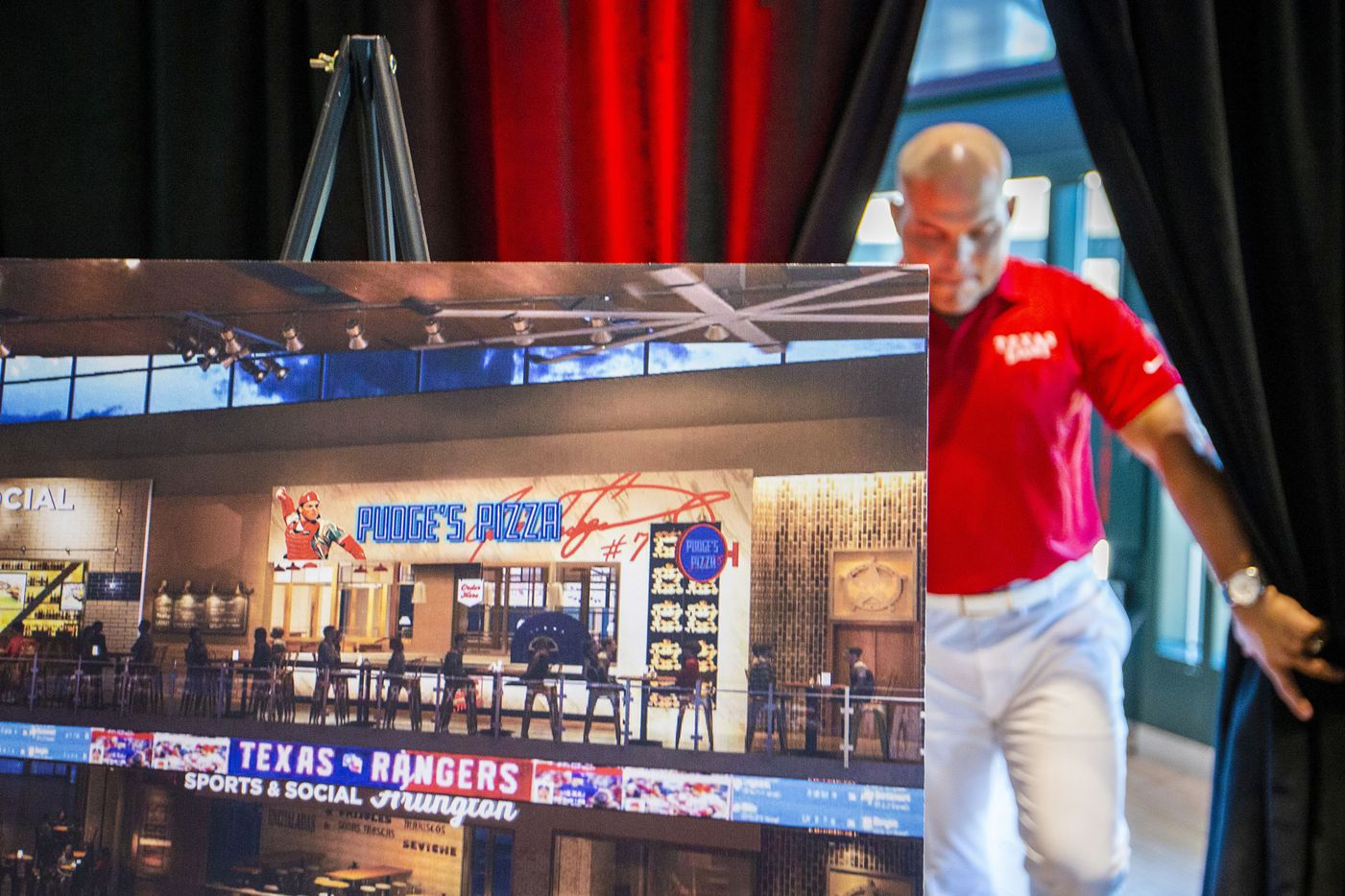 """Hall of Fame Texas Rangers catcher Ivan """"Pudge"""" Rodriguez emerges from a curtain behind a rendering of Pudge's Pizza, a  restaurant at the Texas Live! development during a press event at Globe Life Park."""