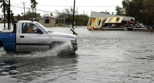 Una camioneta se desplaza por el agua frente a una casa dañada tras el paso del huracán Harvey, el sábado 26 de agosto de 2017, en Aransas Pass, Texas. El huracán destruyó casas y negocios, y causó lluvias y ventarrones que afectaron a los conductores, los cuales tuvieron que salirse del camino porque no podían ver nada frente a ellos, indicaron las autoridades. Foto AP
