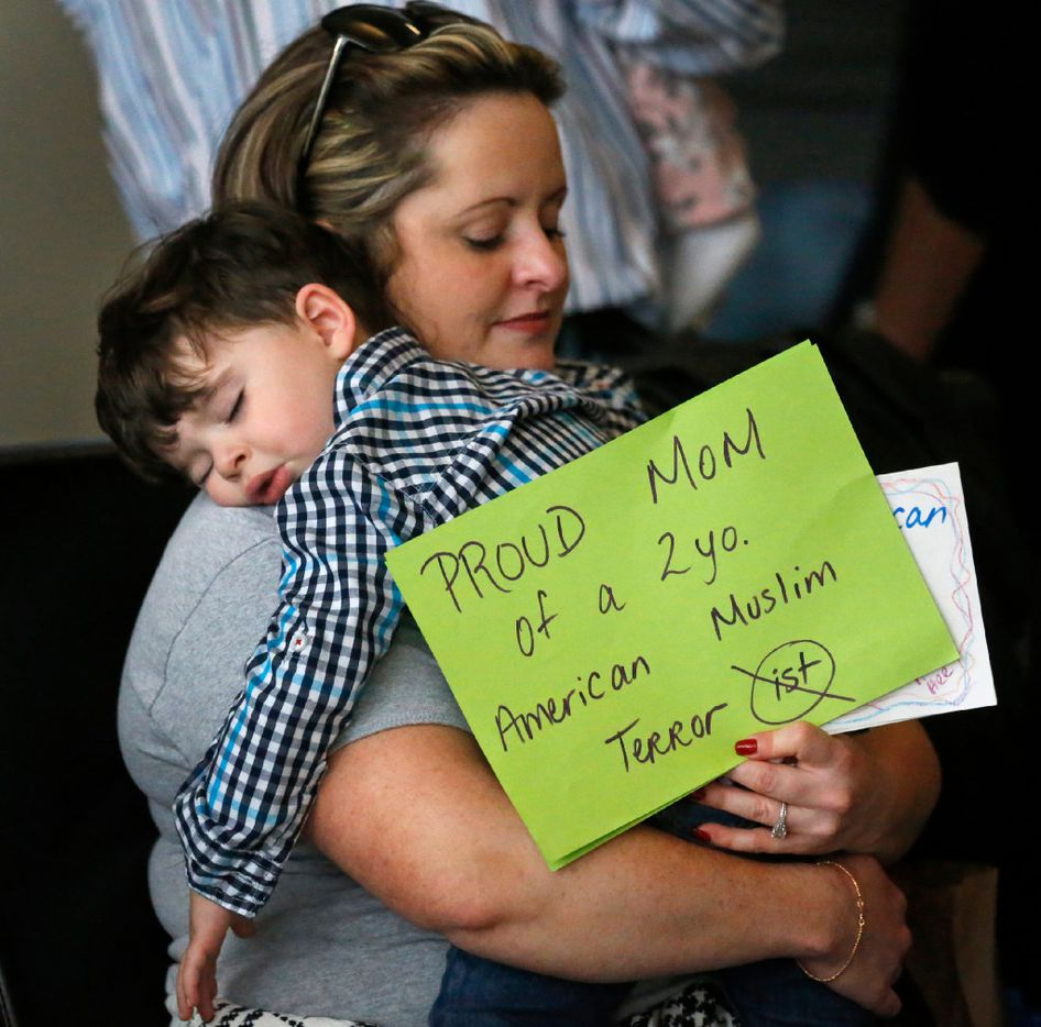 Casey Sabti and her two-year-old son Laith of Dallas take a break from the protest at DFW Airport on Sunday, January 29, 2017. (Louis DeLuca/The Dallas Morning News)