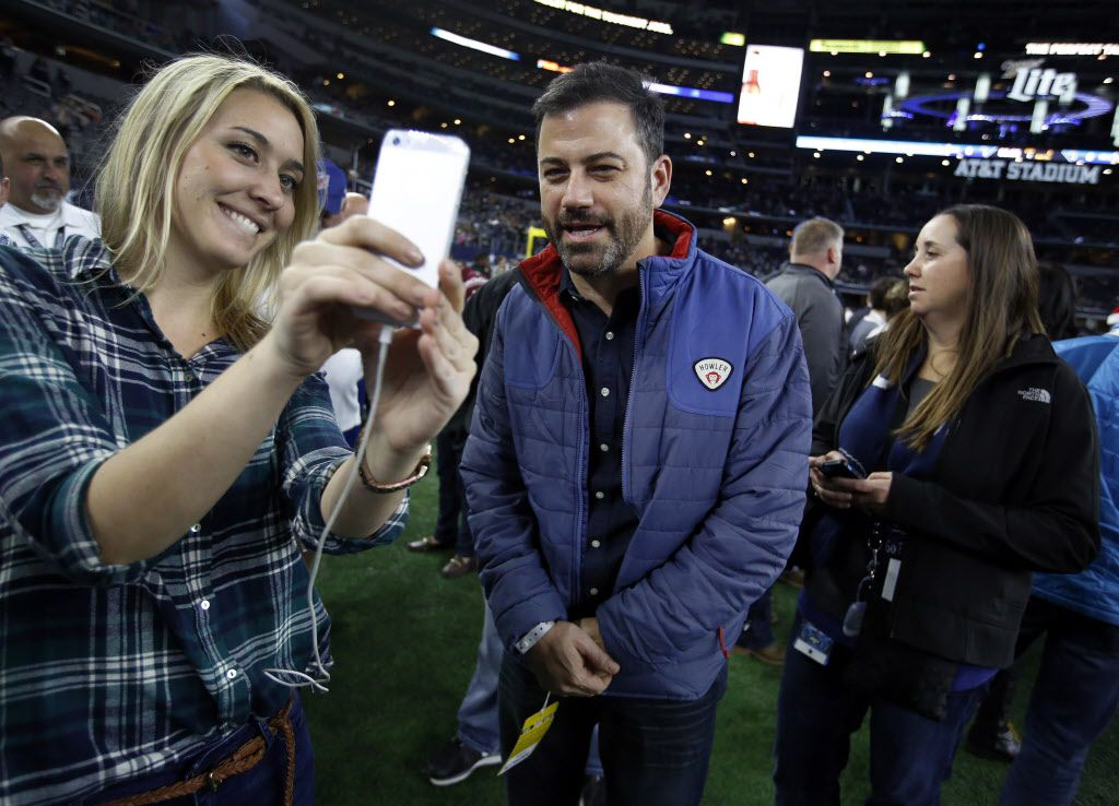 Talk show host Jimmy Kimmel (center) does a snap chat for the NFL Network with social media worker Amanda Carey (left) on the sideline before the Dallas Cowboys game with the New York Jets  at AT&T Stadium in Arlington, Texas, Saturday, December 19, 2015.