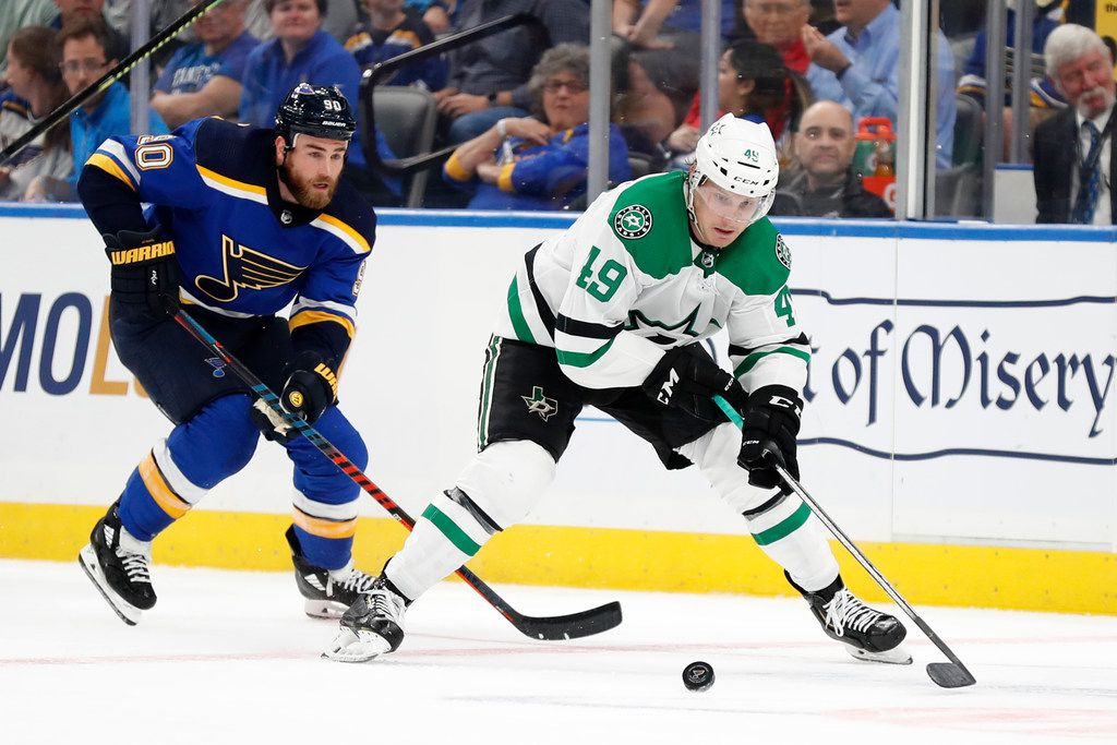 Dallas Stars' Rhett Gardner (49) and St. Louis Blues' Ryan O'Reilly chase after a loose puck during the first period of an NHL preseason hockey game Tuesday, Sept. 24, 2019, in St. Louis.