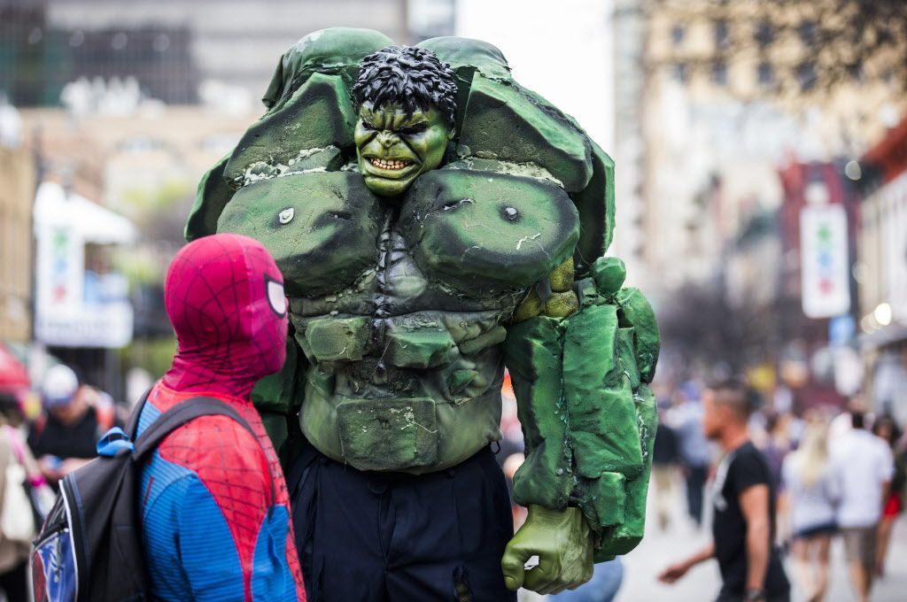 Street performers dressed as The Hulk and Spiderman chat on Sixth Street.