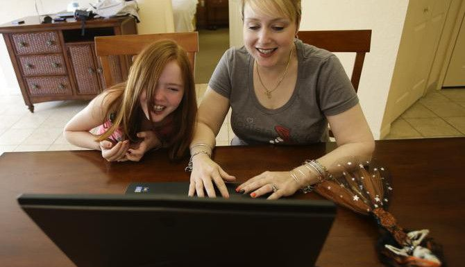 """<137>In this Monday, Oct. 27, 2014 photo, Gracie Hunter, left, and her Mom, Melissa watch a YouTube video of a toy review while on vacation in Kissimmee, Fla. The mother-daughter duo, stars of the """"Mommy and Gracie"""" YouTube show, review dolls for kids. (AP Photo/John Raoux)<137><137><252><137>Gracie Hunter (izq.) y su madre Melissa son las estrellas realizan críticas a muñecas para niñas en """"Mommy and Gracie"""" en YouTube. (AP/JOHN RAOUX)"""