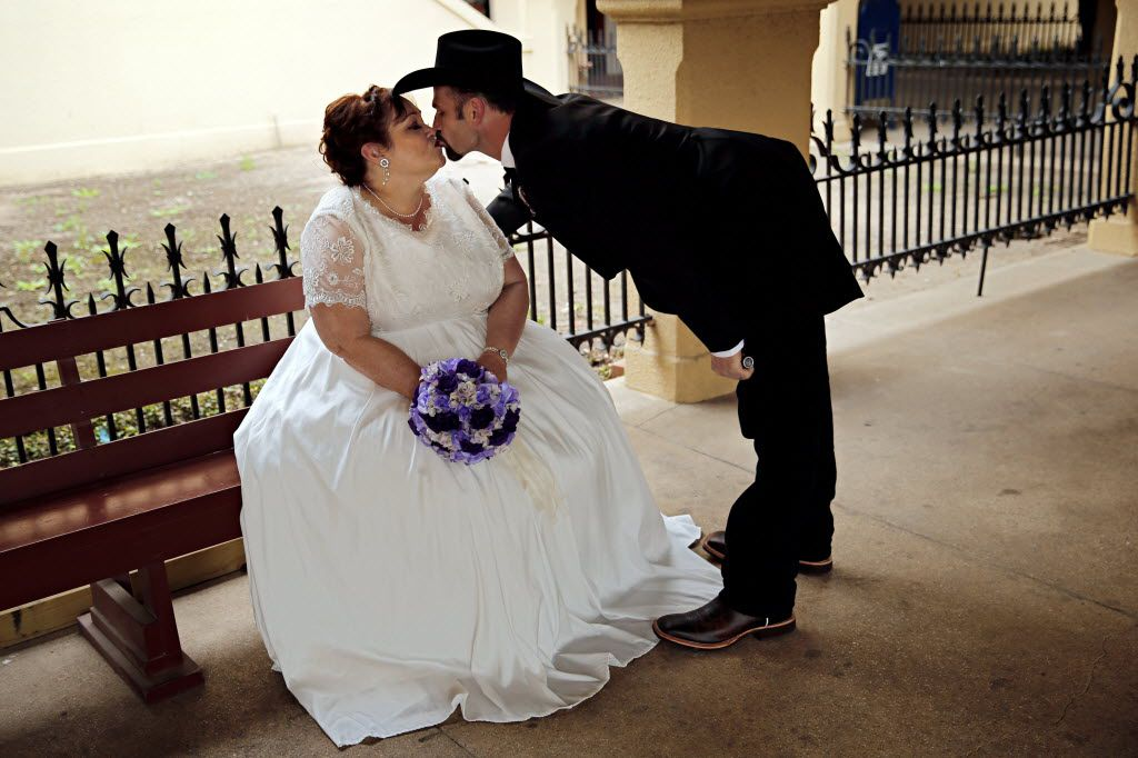 Michael Hull (right) leans over to kiss his soon-to-be bride Michelle Marshall before a mass wedding at the Fort Worth Stockyards Saturday, December 13, 2014 in Fort Worth, Texas.