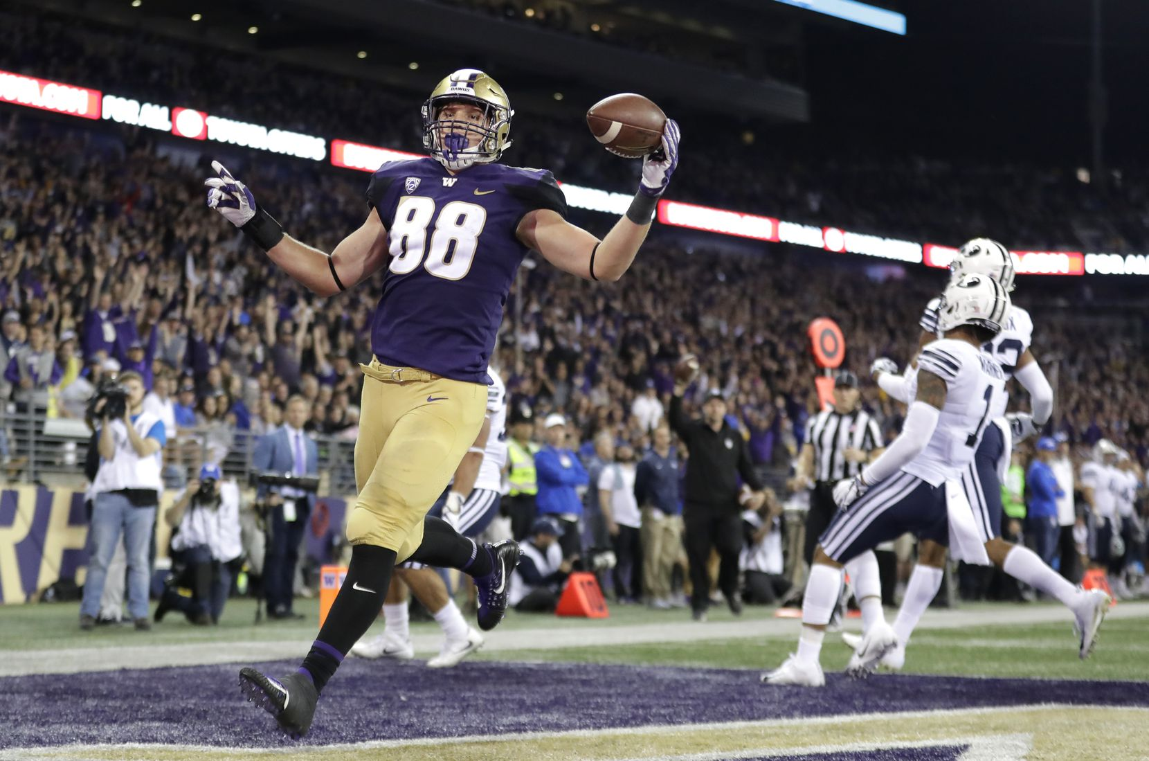 FILE - Washington tight end Drew Sample, left, runs for a touchdown after a pass reception against BYU during the second half of an NCAA college football game, Saturday, Sept. 29, 2018, in Seattle. (AP Photo/Ted S. Warren)