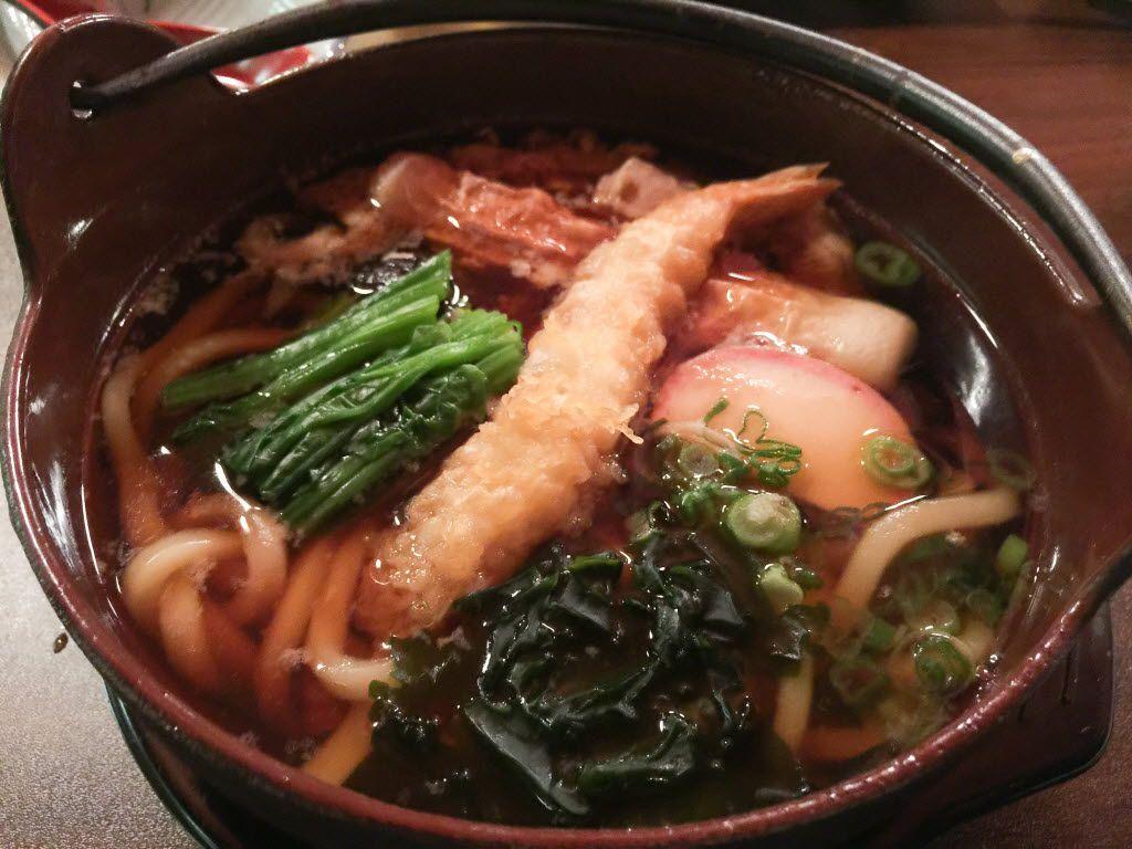Nabeyaki udon is garnished with greens, shrimp tempura, fish cake and more.