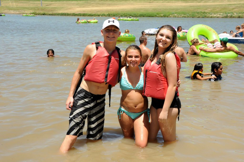 Siblings Cory Fisher, Allyson Meek, and Rilie Williams-France swim in the Trinity River at Sunday Funday at Panther Island Pavilion in Fort Worth on July 19.