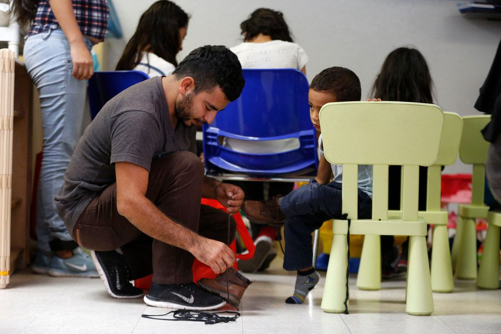 An immigrant puts shoelaces back on his child's shoes at the Humanitarian Respite Center in McAllen, Texas, on June 10. Their laces and property were put in a bag while being detained by ICE.
