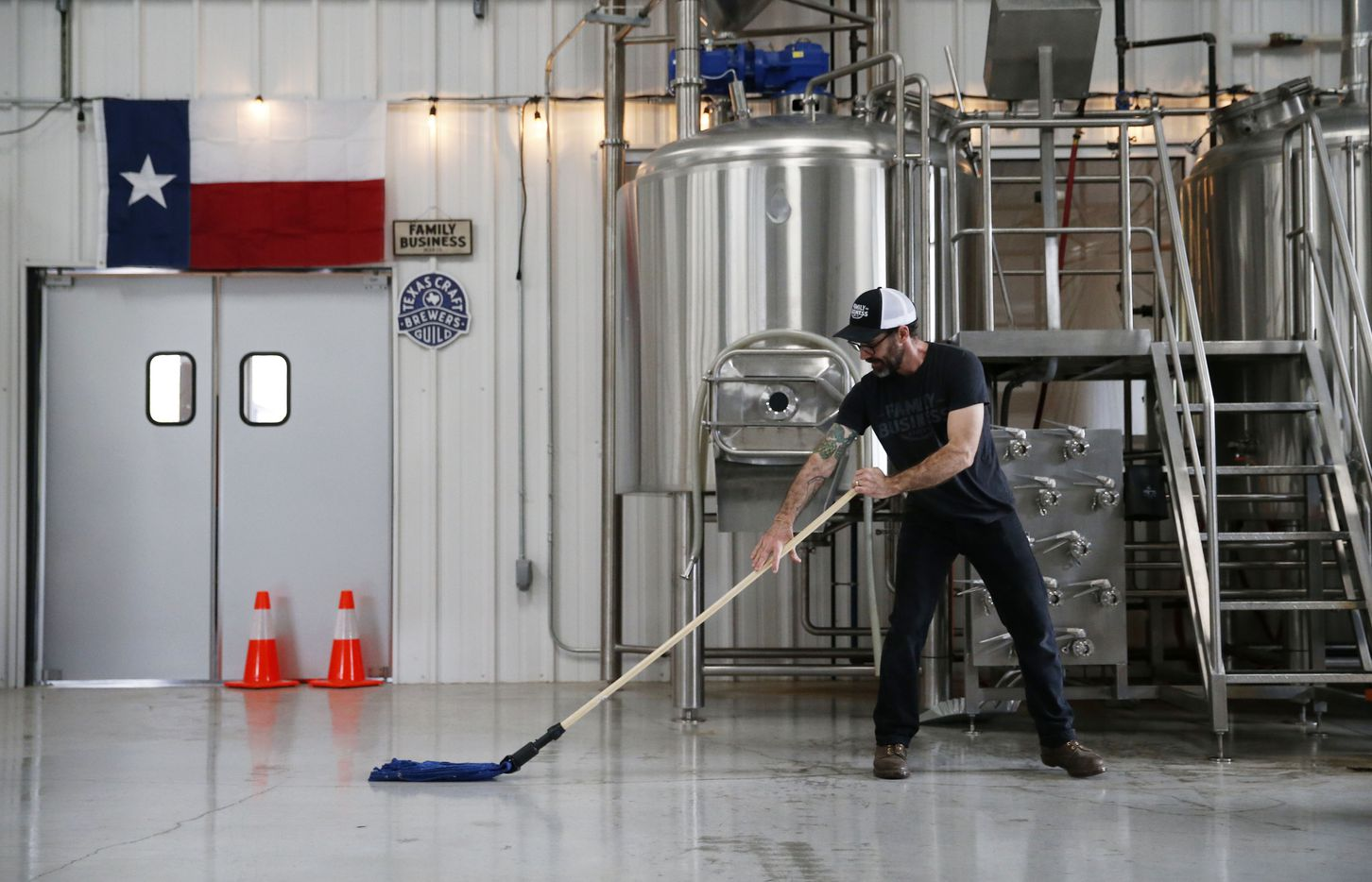 Head brewer Nate Seale mops the floor of the brewhouse at Family Business Beer Company.