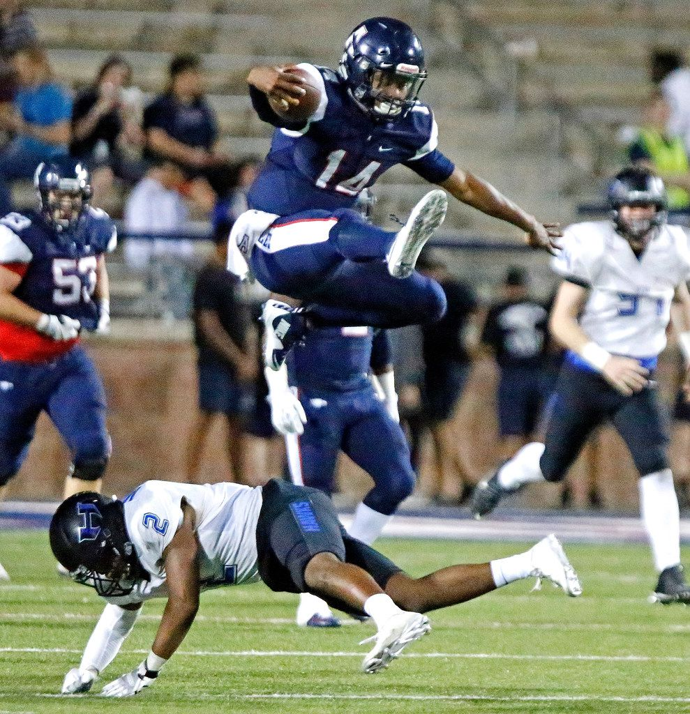 Allen High School quarterback Grant Tisdale (14) hurdles Hebron High School defensive back Demario Montez (2) during the first half as Allen High School hosted Hebron High School in a Class 6A Division I first round playoff game at Eagle Stadium in Allen on Friday night, November 17, 2017. (Stewart F. House/Special Contributor)