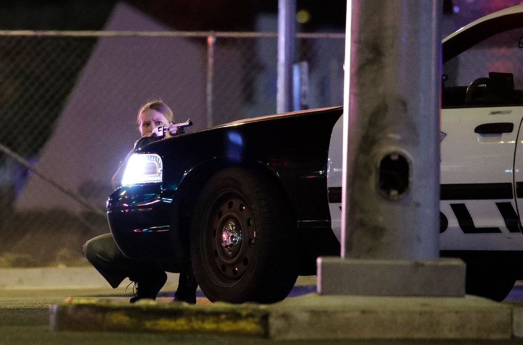 A police officer takes cover behind a squad car during a shooting near the Mandalay Bay resort and casino on the Las Vegas Strip.