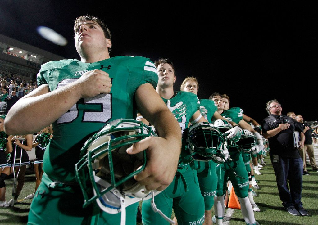 Members of the Southlake Carroll Dragons pause for the playing of the national anthem prior to the opening kickoff against  Flower Mound Marcus. The two teams played their District 5-6A football game at Dragon Stadium in Southlake on October 20, 2017. (Steve Hamm/Special Contributor)