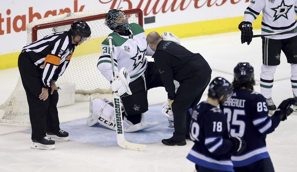 Dallas Stars goaltender Ben Bishop (30) is attended to by team staff for an apparent injury after making a glove save against the Winnipeg Jets during the first period of an NHL hockey game Sunday, March 18, 2018, in Winnipeg, Manitoba. (Trevor Hagan/The Canadian Press via AP)