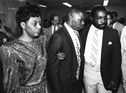 Gary Edwards, the former Carter HS football player, leaves court with his mother Sue and father Thurman on July 14, 1989, after he pled guilty to armed robbery before Judge Joe Kendall.