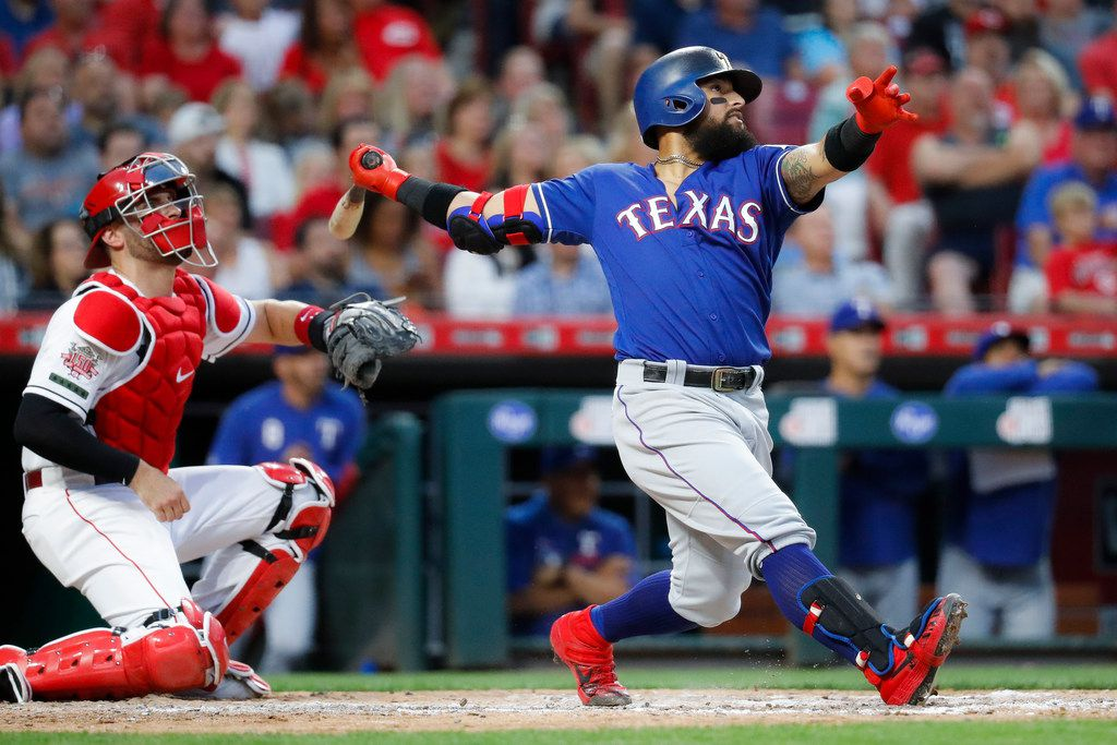 CORRECTS TO GRAND SLAM NOT THREE-RUN HOME RUN - Texas Rangers' Rougned Odor, right, hits a grand slam off Cincinnati Reds relief pitcher Wandy Peralta in the fifth inning of a baseball game, Friday, June 14, 2019, in Cincinnati. (AP Photo/John Minchillo)