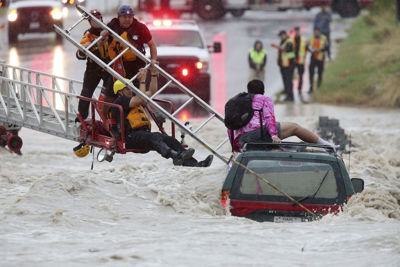 San Antonio Fire Department personnel rescue a man trapped on top of his submerged vehicle at a low water crossing on Pinn Road by SH 151, Monday, August 7, 2017.