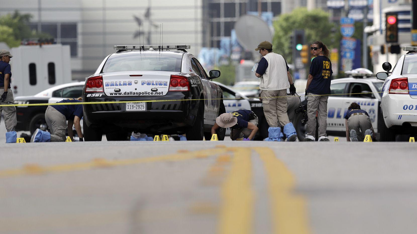 Investigadores trabajan en el centro, donde las calles permanecen cerradas tras el ataque  en el que un francotirador mató  a cinco policías.