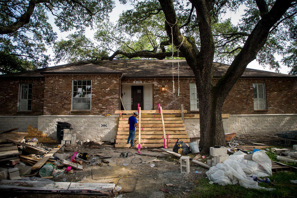Workers erect a new front stairs for a house in the 4900 block of Braesvalley Drive, that has been raised as part of home elevation efforts in the Meyerland neighborhood, a few blocks from Brays Bayou, on Saturday, Aug. 11, 2018, in Houston. The area was flooded due to Hurricane Harvey.  (Smiley N. Pool/The Dallas Morning News)
