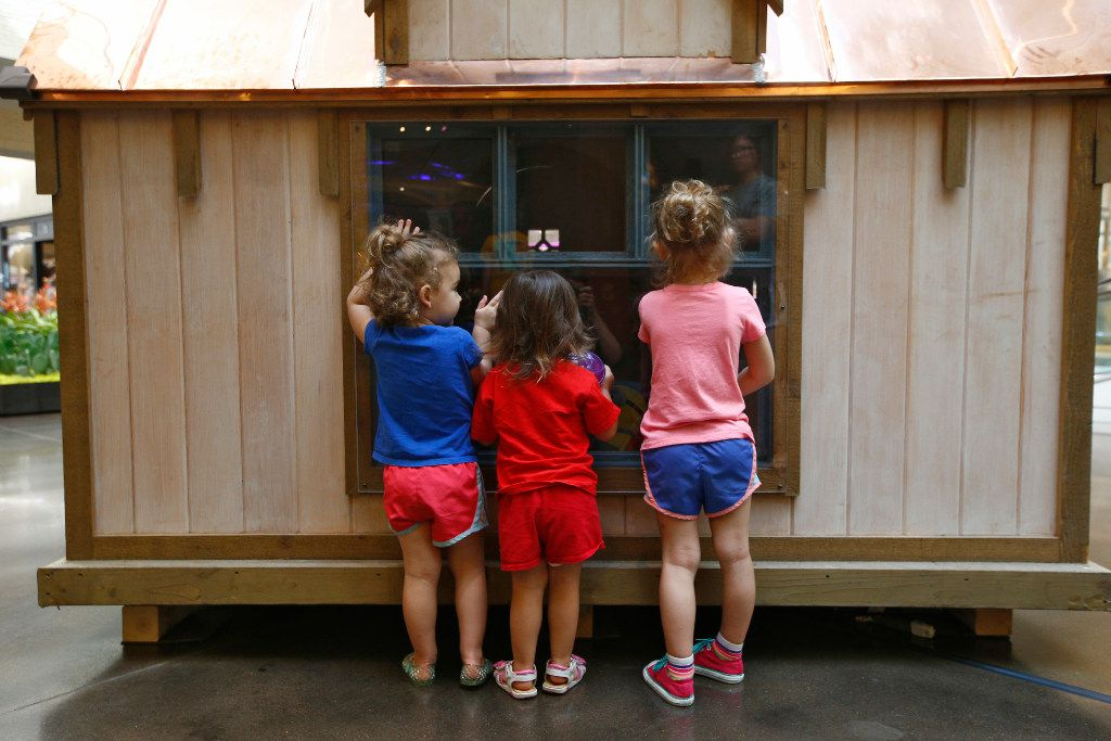 Sasha Nanney, 2, (from left) Lula Doenges, 2, and Luisa Doenges, 4, look into the Whimsical Cottage as part of the Dallas CASA's Parade of Playhouses at NorthPark Center in Dallas on July 7, 2017.  (Nathan Hunsinger/The Dallas Morning News)
