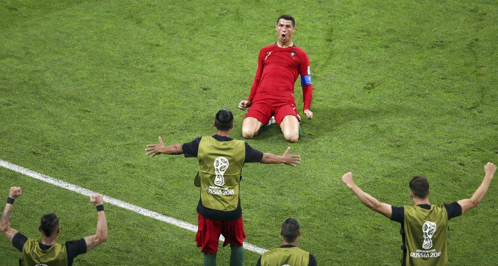 Cristiano Ronaldo se desliza de rodillas tras marcar el segundo gol de Portugal en el partido contra España por el Grupo B del Mundial en Sochi, Rusia, el viernes 15 de junio de 2018. (AP Foto/Thanassis Stavrakis)