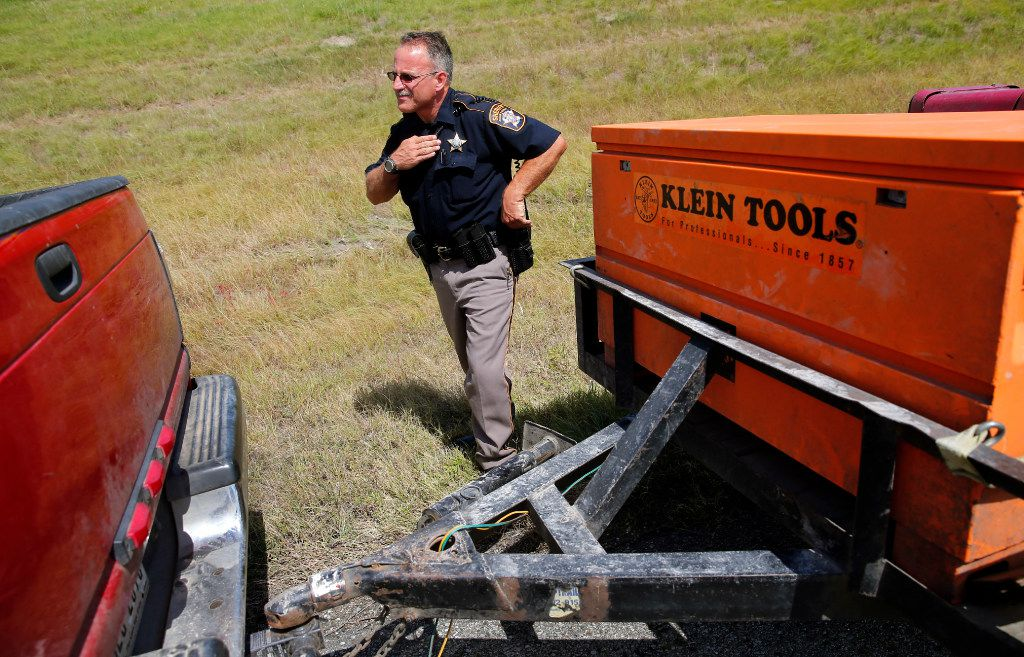 Collin County Sheriff's Deputy Kelly Reynolds takes a position behind a pickup after he and Rodney Tackett pulled over a pickup and trailer on U.S. Highway  75 in Collin County on Tuesday.