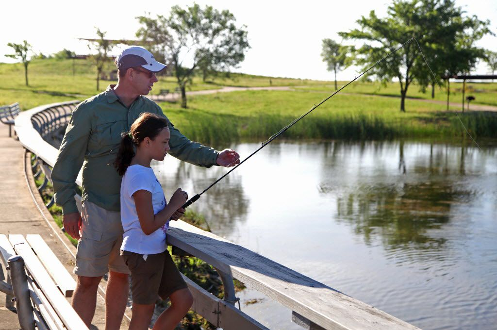 Ross Bond (left) of Coppell gave pointers to his daughter Alexandra, at Brockdale Park on Lavon Lake in Lucas during Rods n' Raptors Kids Fishing Derby.