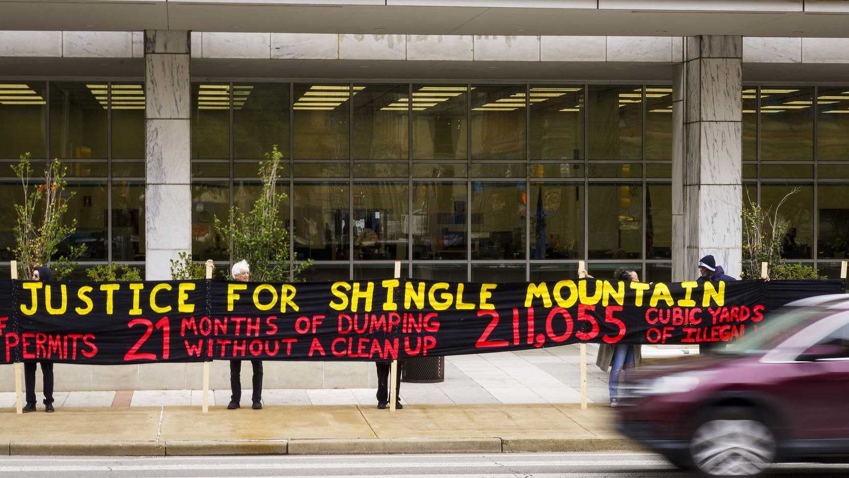 Activists hold a banner reading outside the George L. Allen Sr. Courts Building on Friday. An hour later, the judge gave them what they wanted. Sort of.