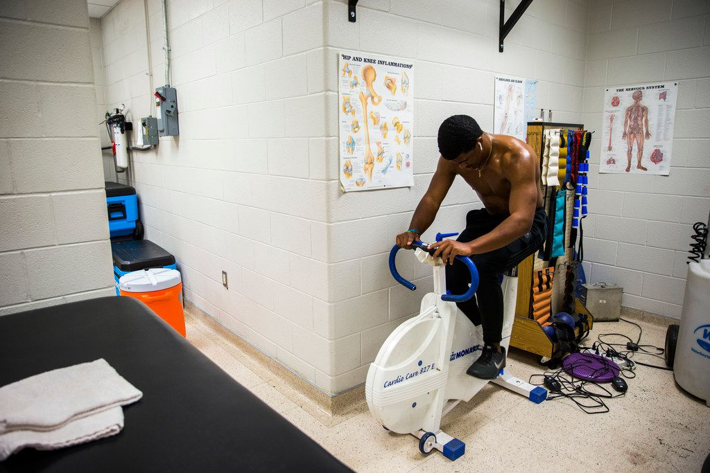 Mansfield Legacy football player Jalen Catalon does a bike workout in the training room on Thursday, January 31, 2019 at Mansfield Legacy High School in Mansfield. Catalon's senior football season was ended by a torn left ACL. After surgery and months of rehab, he will sign to play football in the fall at University of Arkansas. (Ashley Landis/The Dallas Morning News)