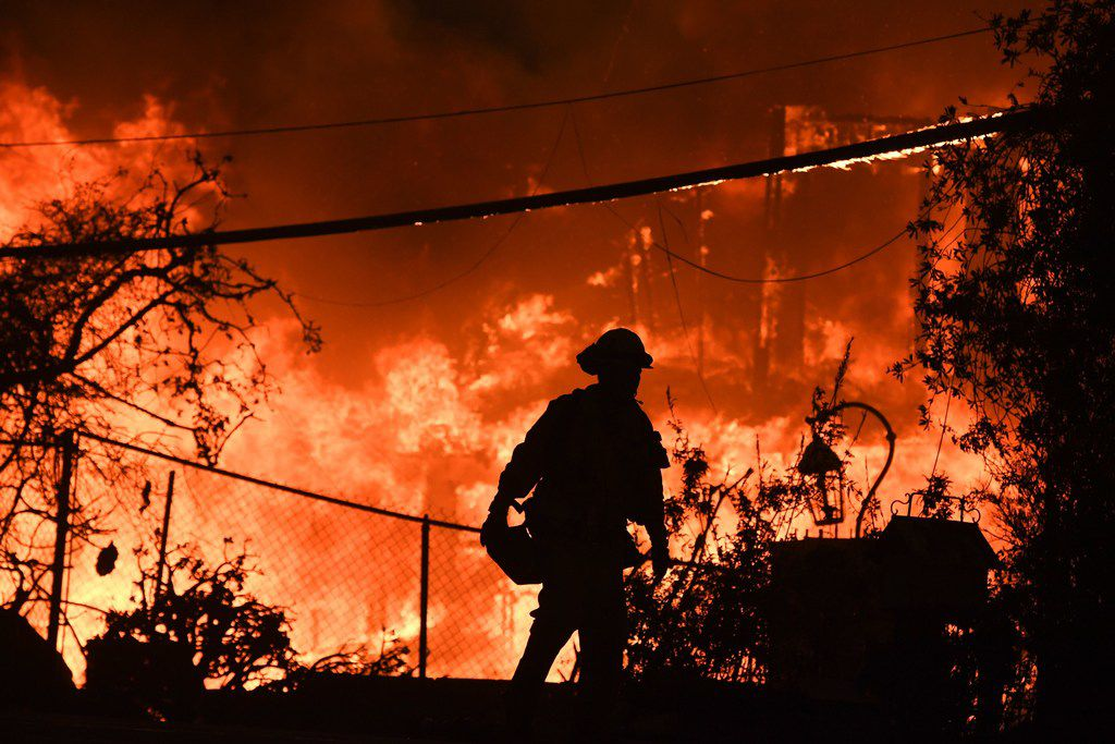 A firefighter is silhouetted by a burning home along Pacific Coast Highway (Highway 1) during the Woolsey Fire in Malibu, Calif., on Nov. 9.