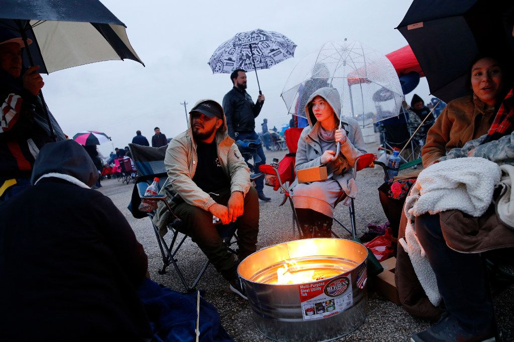 Caitlin Petty of Mansfield (center, right) and Michael Lopez of Dallas (center, left) take cover from the light rain and keep warm around a fire before lighting paper lanterns and releasing them into the night sky during the Lantern Festival at Texas Motorplex in Ennis, Texas, Saturday, March 4, 2017. (Tom Fox/The Dallas Morning News)