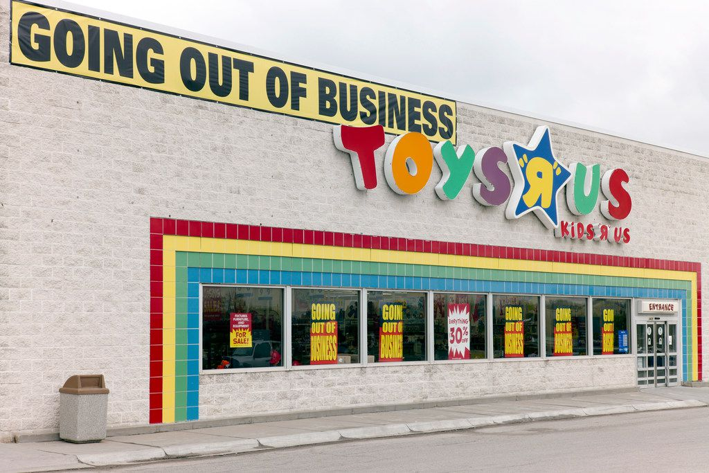 """A """"Going Out Of Business"""" sign hangs over the Toys R Us store logo in Omaha, Neb."""