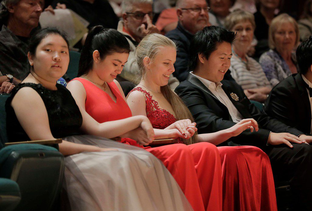 JiWon Yang from South Korea, Avery Gagliano from the United States and Eva Gevorgyan from Russia/Armenia and Shuan Hern Lee wait for announcement of the finalists of the Cliburn International Junior Piano Competition and Festival at Caruth Auditorium on the campus of SMU in Dallas.
