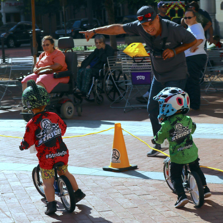 """Mateo Montaño corre en su """"balance bike"""" mientras que su papá, Pepe Montaño, le hecha porras desde la línea de banda. Foto de Javier Giribet para Al Día."""