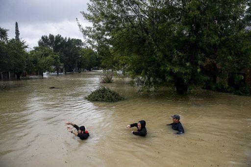 Tres personas caminan con el agua a la altura del pecho por Pine Cliff Drive, mientras Addicks Reservoir se acerca al máximo de su capacidad tras las constantes e intentas lluvias arrojadas por la tormenta tropical Harvey, en Houston. Foto AP