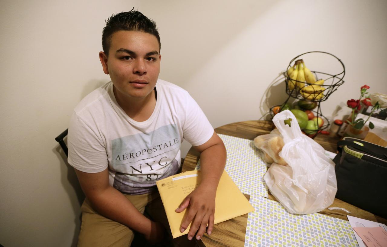 Jonathan López, de Des Moines, Iowa, sostiene un folder con los documentos de su petición de asilo en Clive, Iowa. El pedido de López fue rechazado y el adolescente planea apelar en febrero. (AP/CHARLIE NEIBERGALL)