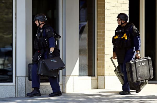 Police officers carried cases as they entered a building during a standoff with an armed man.