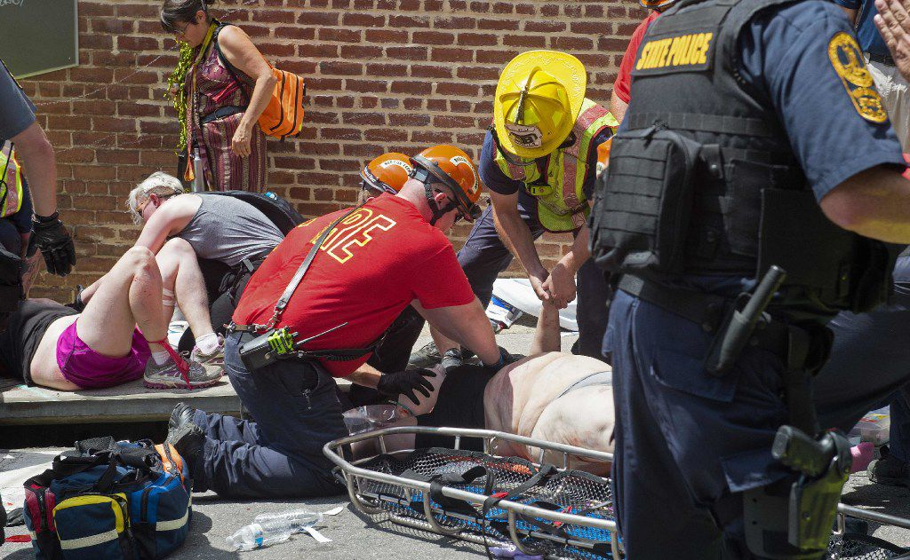 Injured people receive first aid after a car ran into a crowd of protesters in Charlottesville, Va., on Aug. 12. A vehicle plowed into a crowd of people Saturday at a Virginia rally where violence erupted between white supremacist demonstrators and counterprotesters, witnesses said. One person was killed.
