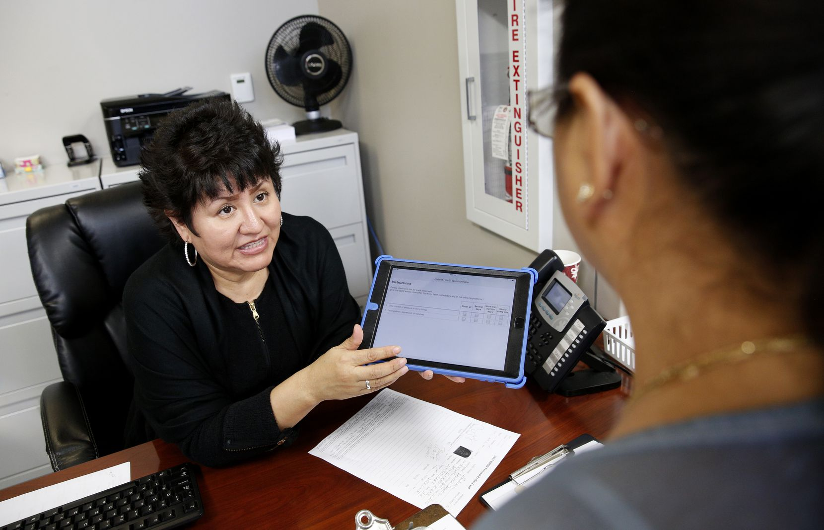 Leticia Balderas, clinic receptionist, explains how to fill out the VitalSign6 survey to patient Maria J. Maldonado at Brother BillÕs Helping Hand in Dallas.