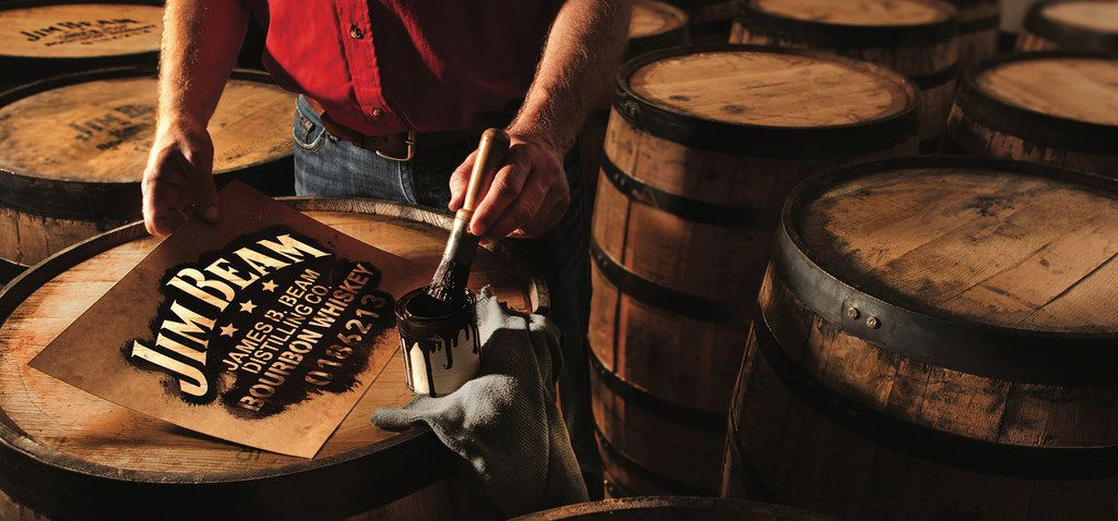 A Jim Beam worker paints the tops of barrels. The company offers tours to the public at Jim Beam American Stillhouse in Clermont, Ky.